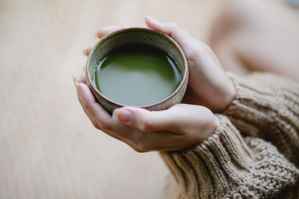 person holding a cup of matcha tea
